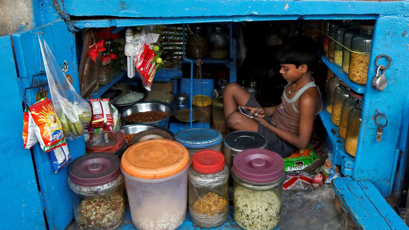 A boy uses a mobile phone as he sits inside his father's snacks shop along a road in Kolkata, India, February 22, 2016. REUTERS/Rupak De Chowdhuri/File Photo - RTX2EFD0